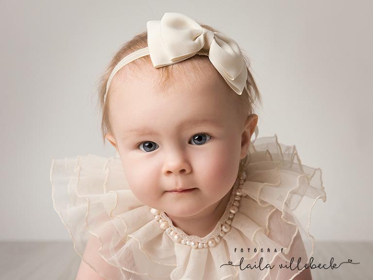 Närbild på baby i outfit med tyll och pärlor samt hårrosett