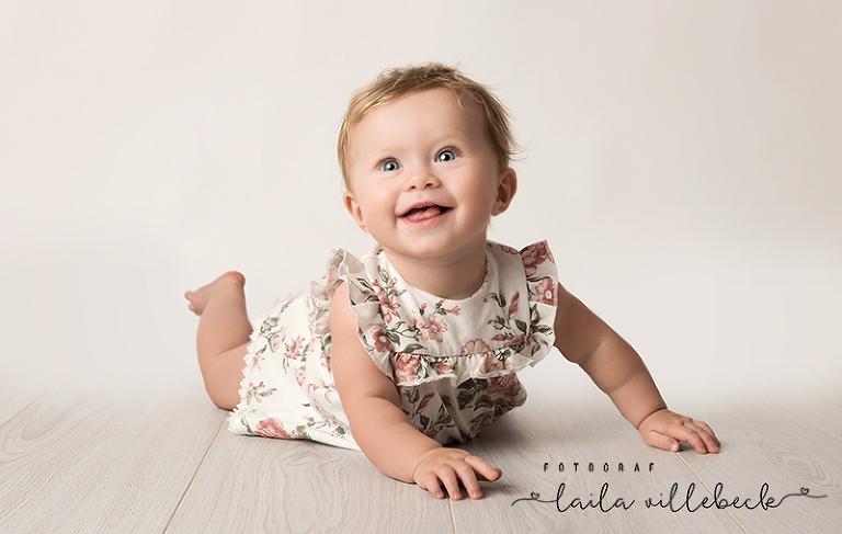 Glad och söt tjej blir fotograferad i studion