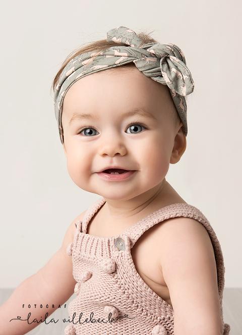 Babyfotografering av glad liten tjej i rosa hemmastickad byxdress