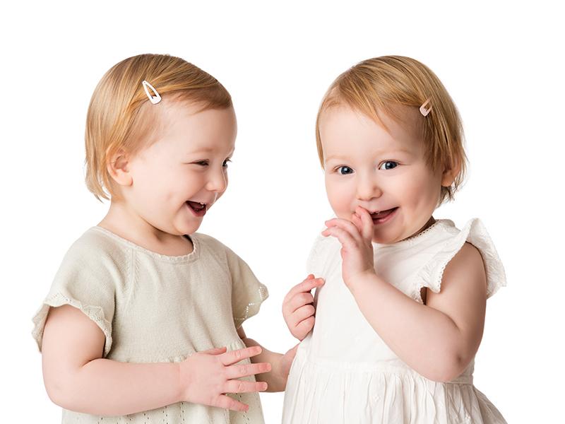 Två glada tvillingflickor busar med varandra framför kameran