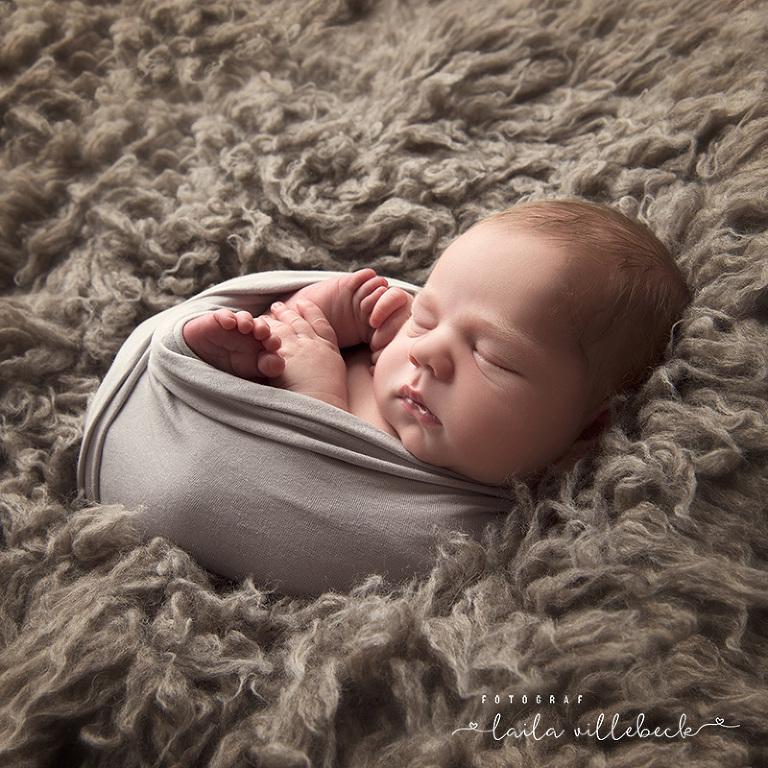 Bebis på grå flokati fäll, inlindad i grå wrap