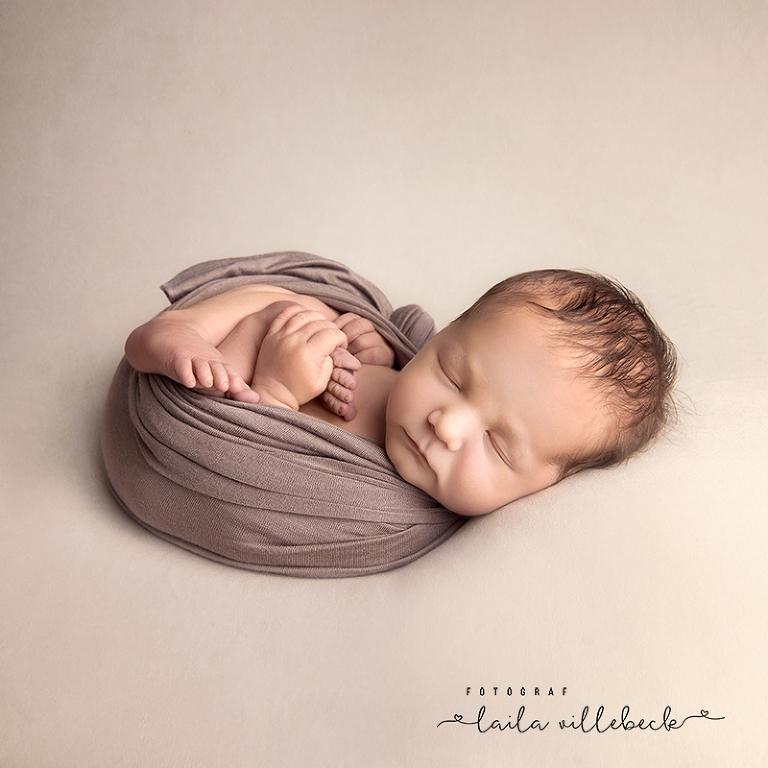 Inlindad nyfödd som håller i foten