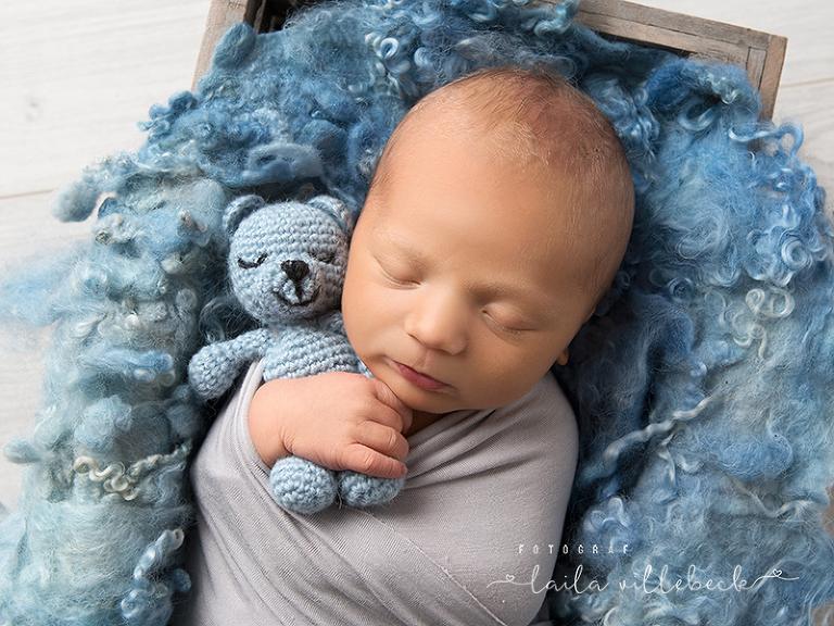 Nyfödd pojke invirad i en grå sjal och sovandes på blå filt med blå nalle i famnen.