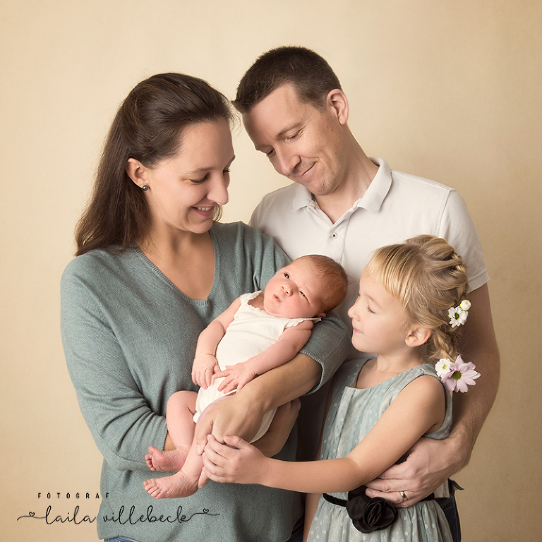 Mamma, pappa, nyfödd, storasyster i en härlig familjebild under nyföddfotografering i studio