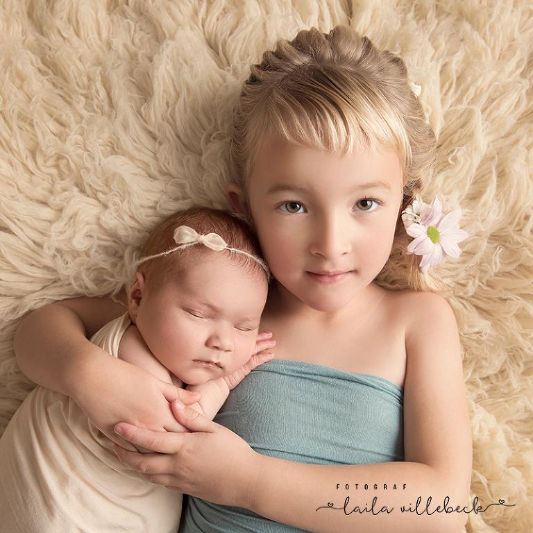 På en cremefärgad fäll ligger Majken och håller stolt nyfödda Ida som sover på hennes arm