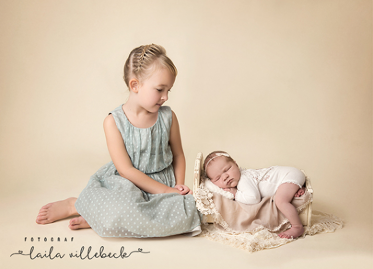 Storasyster Majken tittar stolt och nyfiket på nyfödda lillasyster Ida som sover sött i en liten säng