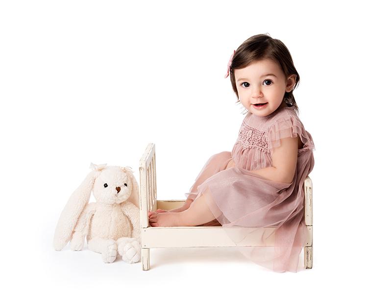 En söt tjej sitter i docksäng med gosedjur bredvid