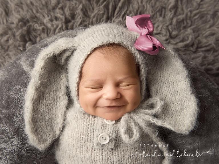 Nyfödd flicka med stort leende i grå kanindräkt
