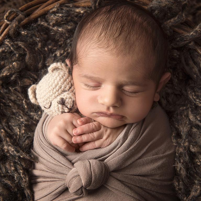 Inlindad och varm sover han tryggt med en liten nalle i händerna