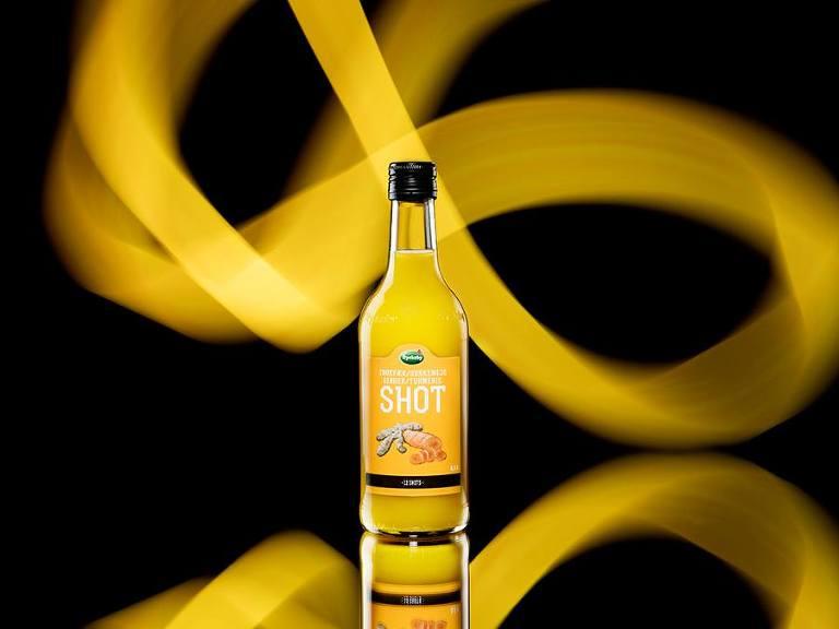 Produktfoto av ingefärashot på spegel med gult mönster i bakgrunden