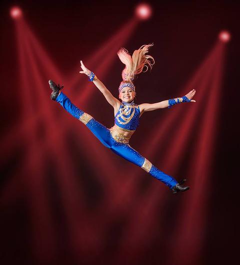 Alicia gör ett splitthopp i sin tävlingsdräkt i blått och guld. I bakgrunden syns rödrosa strålkastare