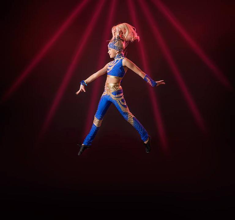 Alicia dansar disco i sin tävlingsdräkt i blått och guld.