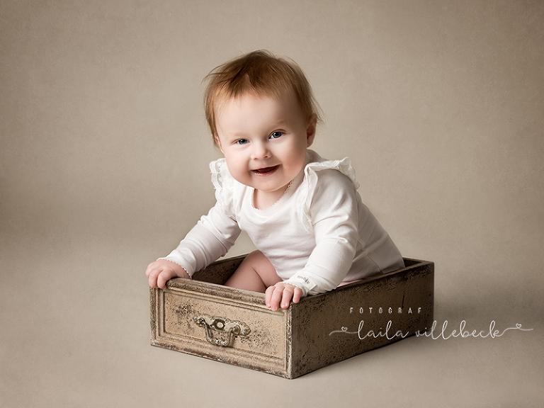 6 månaders bebis sitter i en låda och skrattar.