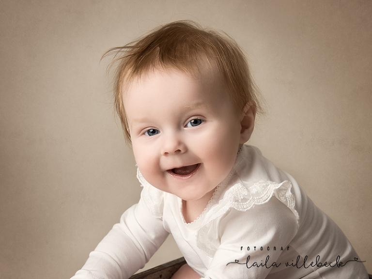 En glad liten tjej i vit spetsbody från Newbie, KappAhl