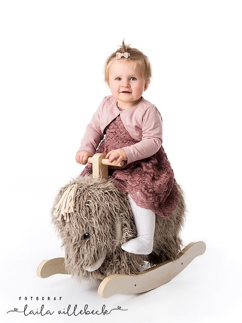 Ellie på sin gunghäst under sin ettårsfotografering hos Fotograf Laila Villebeck i Linköping