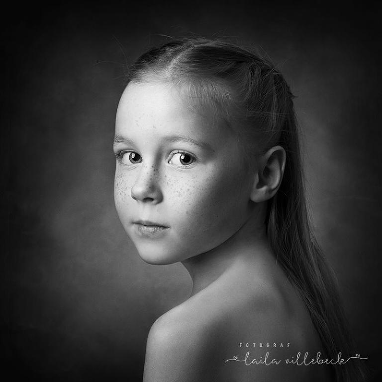 Monokromt fineartporträtt på fräknig flicka