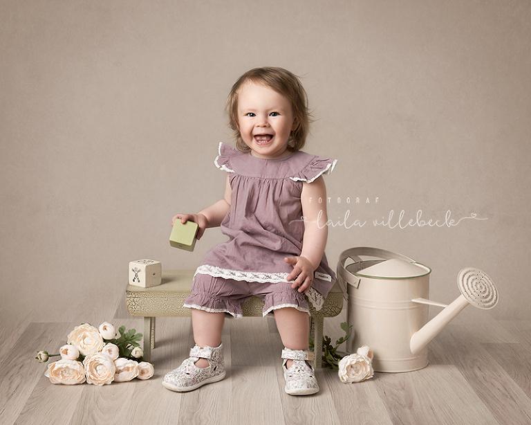 Flicka i lila tunika från KappAhl sitter på en pall i fotografens studio