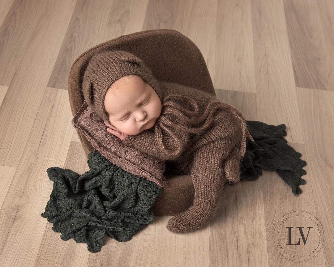 Iza som nyfödd iklädd en liten brun nallekostym i brun fåtölj med grön filt.