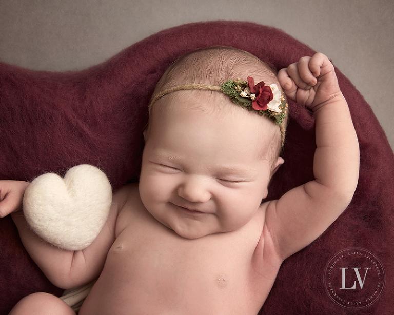En leende nyfödd flicka med ett filtat hjärta i vitt