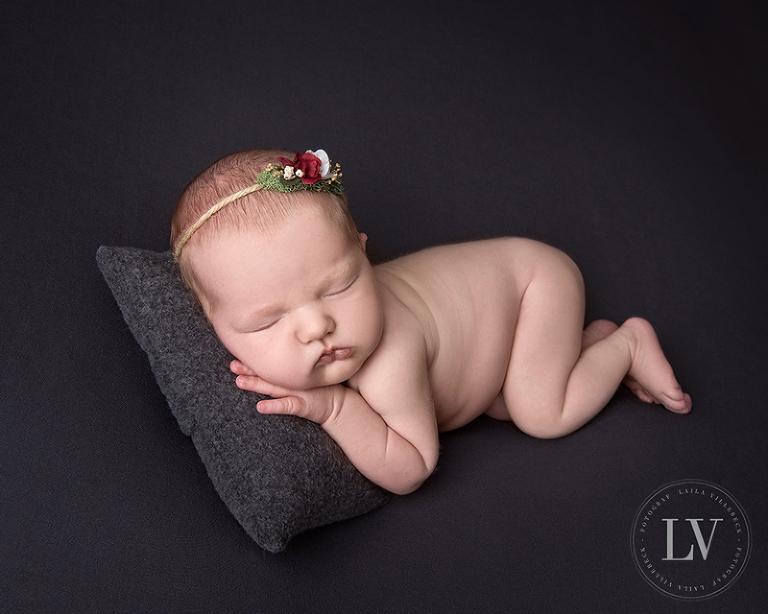 Vilsam bild på sovande nyfödd på grå filt och kudde