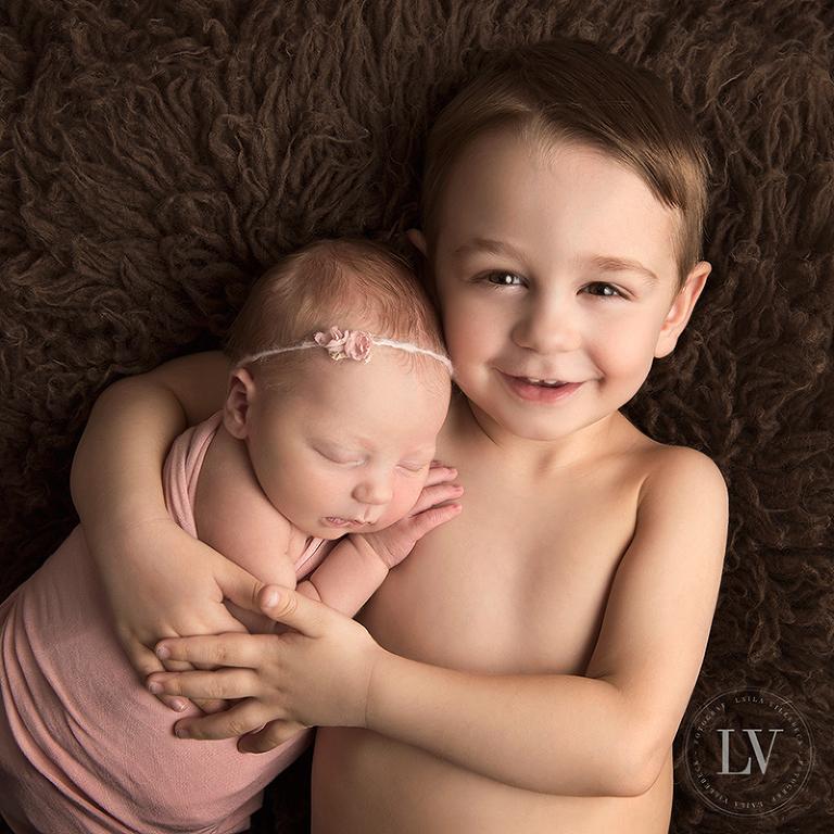 Stolt storebror håller om sin nyfödda lillasyster