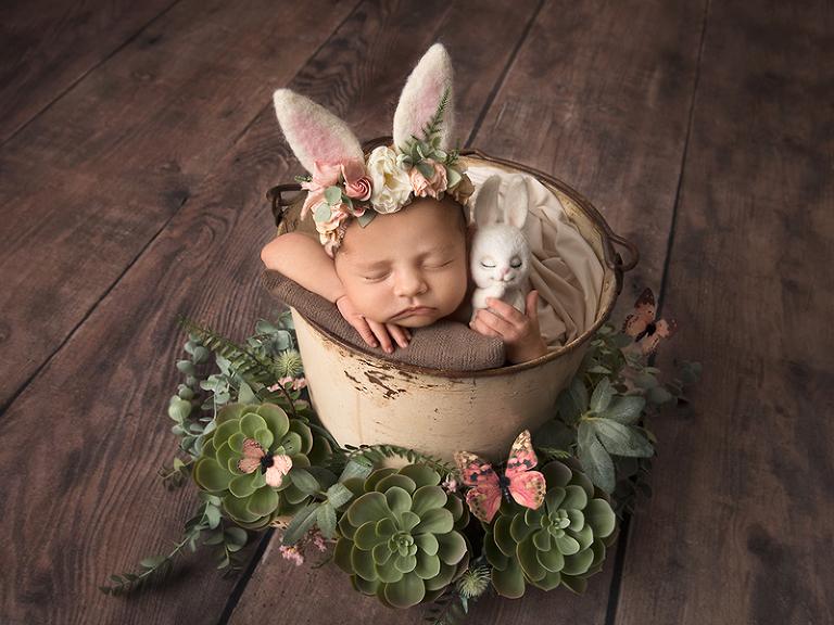 Nyfödd flicka i hink med kaninmössa