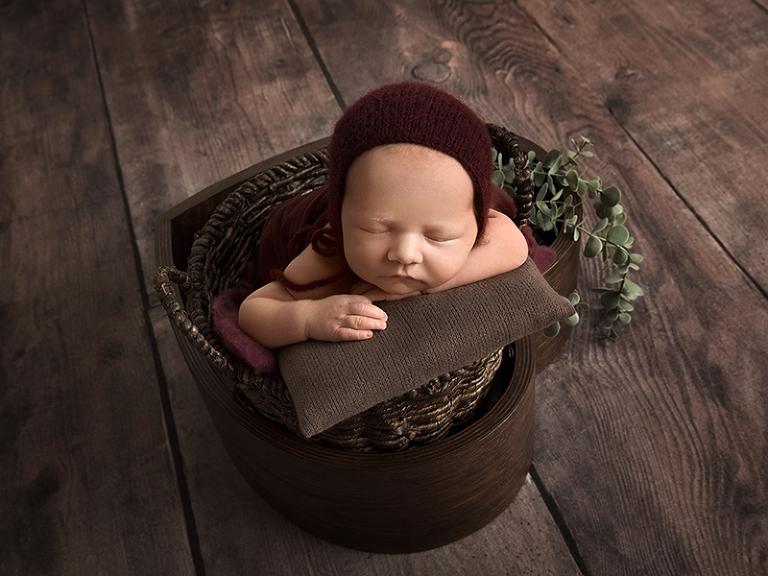 Poserad nyfödd i en korg med hjärtform under en nyföddfotografering