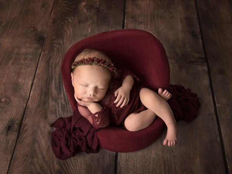 Nyfödd flicka i vinrött sitter och sover i fåtölj under nyföddfotografering