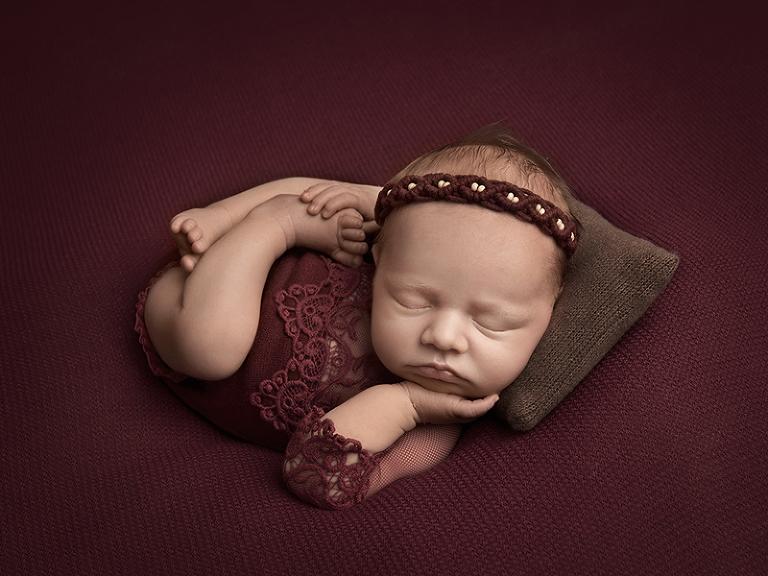 Nyfödd tjej sover i cool pose på en brun kudde och vinröd filt