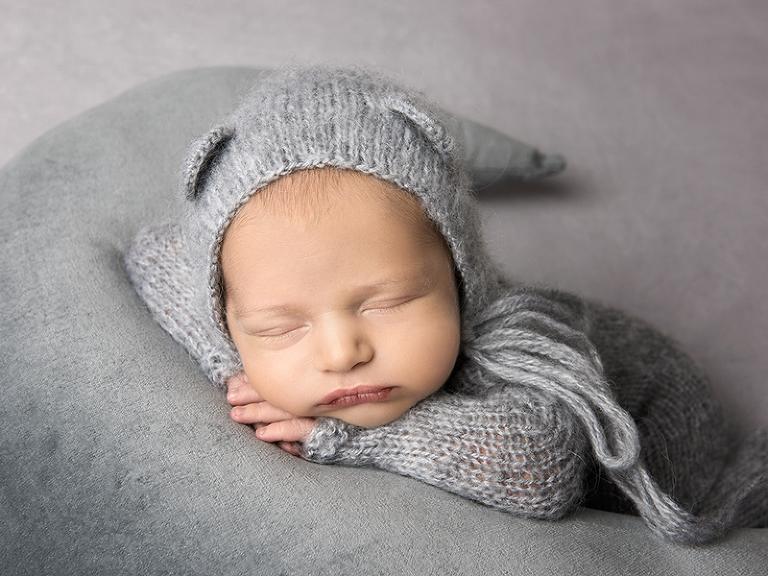 Liten pojke i grå nallemössa med rosett under hakan