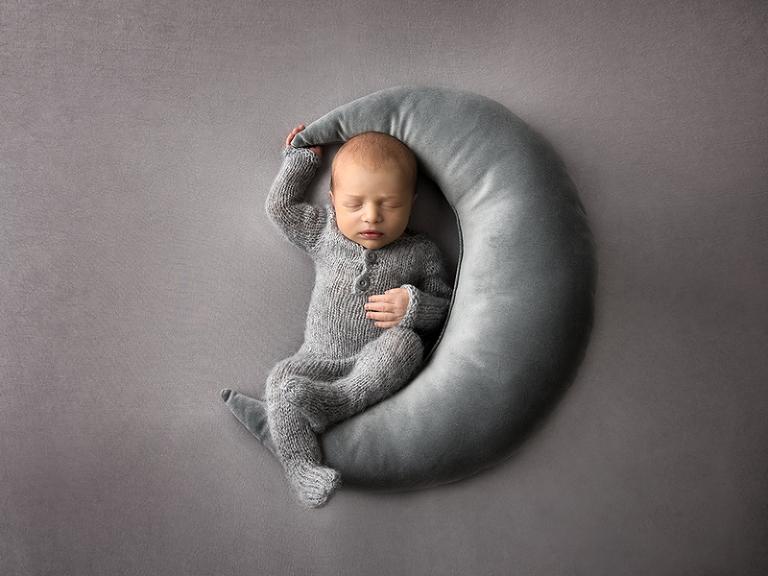 Nyfödd pojke i grått sitter på en måne och håller i månen med höger hand över huvudet