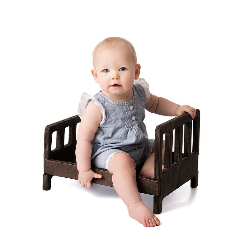 Helkroppsporträtt av en liten flicka som sitter i en brun träsäng och håller i sänggaveln