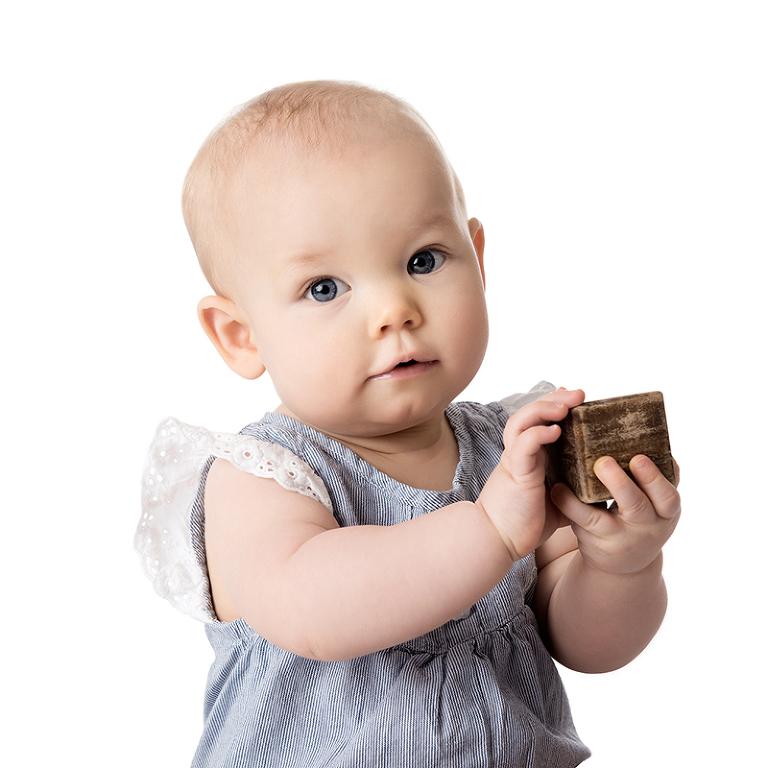 Porträtt av liten flicka som håller upp en kloss i trä