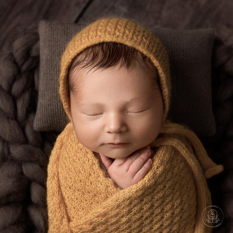 Rofyllt porträtt av en sovande nyfödd pojke iklädd en stickad senapsgul mössa och invirad i en matchande filt.
