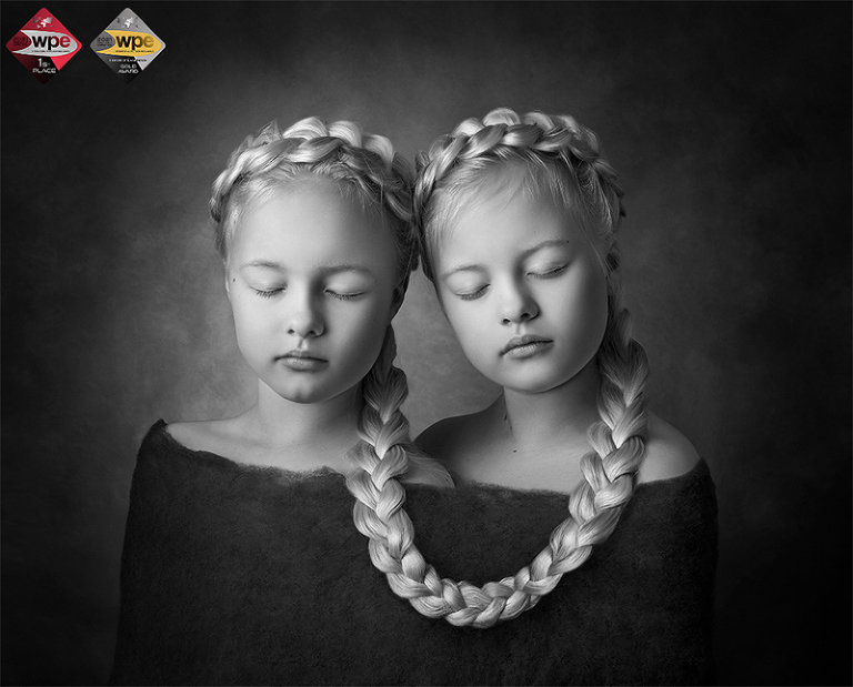 De blonda tvillingarna Märta och Saga sitter ihop med en fläta. Bilden vann barnkategorin i WPE Awards Children First Half 2021