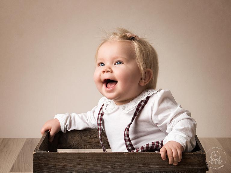 En glad ettåring ler stort när hon sitter i en låda under sin ettårsfotografering.