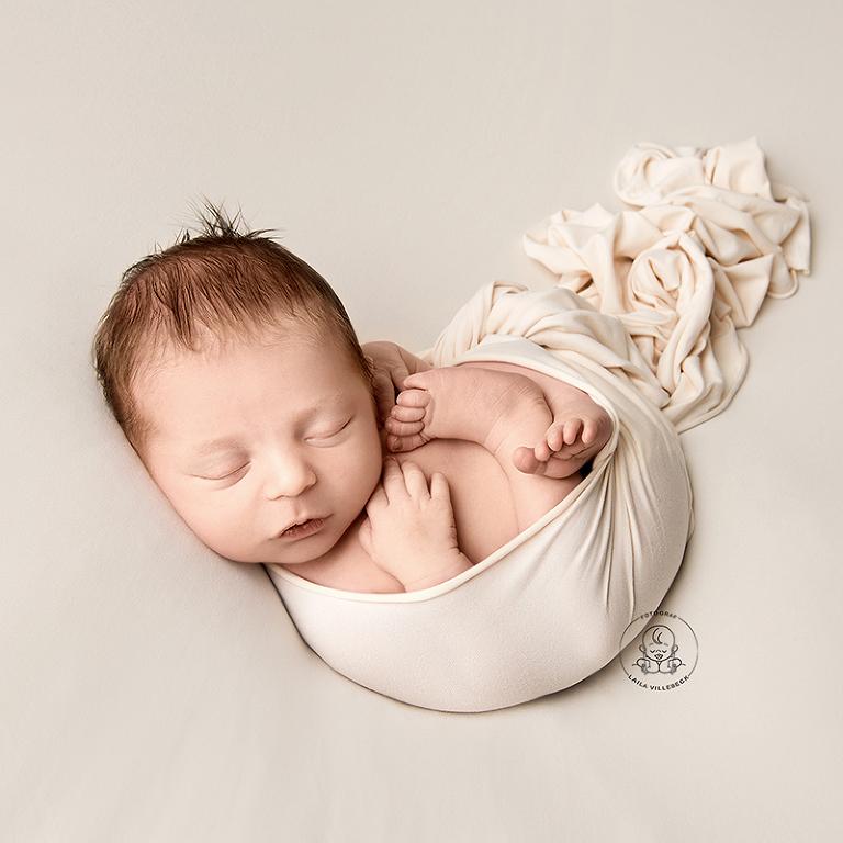 Tryggt inlindad i en vit wrap ligger Ossian och sover.