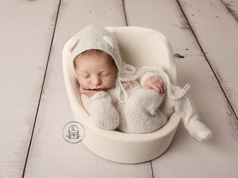 Ossian är bara drygt en vecka gammal, men här halvsitter han i en specialdesignad fåtölj för nyföddfotografering. Han har en liten vit björndräkt på sig.