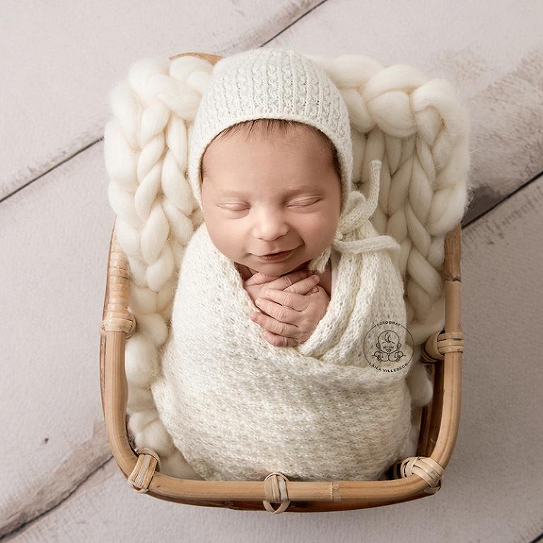 Ossian, 9 dagar, ligger och ler i en korg. Han har en vit mössa, är inlindad i en vit stickad filt och ligger på en chunky blanket i samma vita nyans.