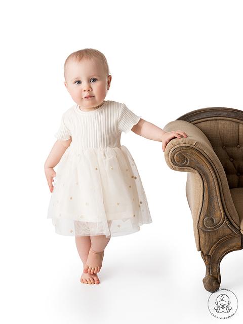 Ettåriga Maja står med ena handen på en soffkant och andra handen på sin fina, vita klänning. Fötterna står lite nätt i kors.
