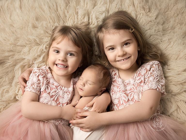 Tre syskon ligger på en cremefärgad fäll.