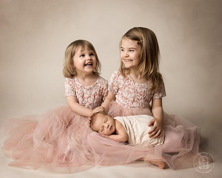 Lycka är att få en lillebror. Det syns i Sagas och Leahs ansikten när de ler stort med lillebror i knät.