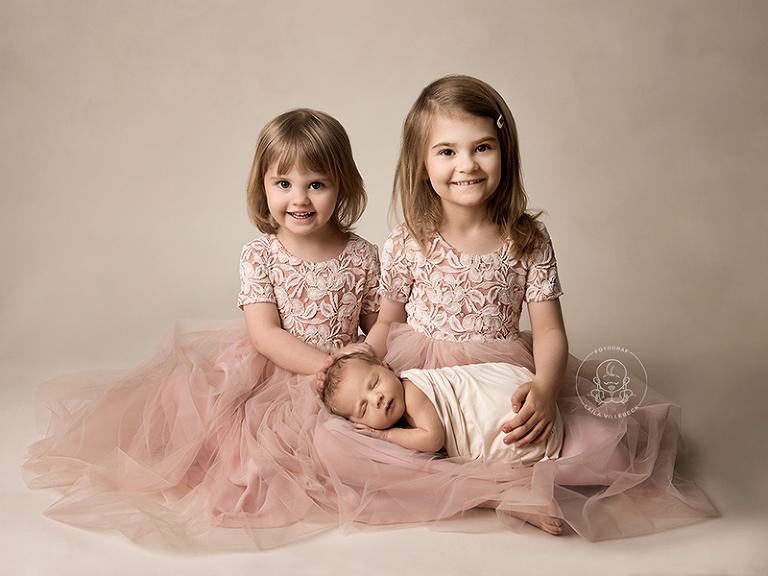 Två söta systrar i likadana rosa tyllklänningar sitter med sin nyfödda lillebror i knät och ler in i kameran
