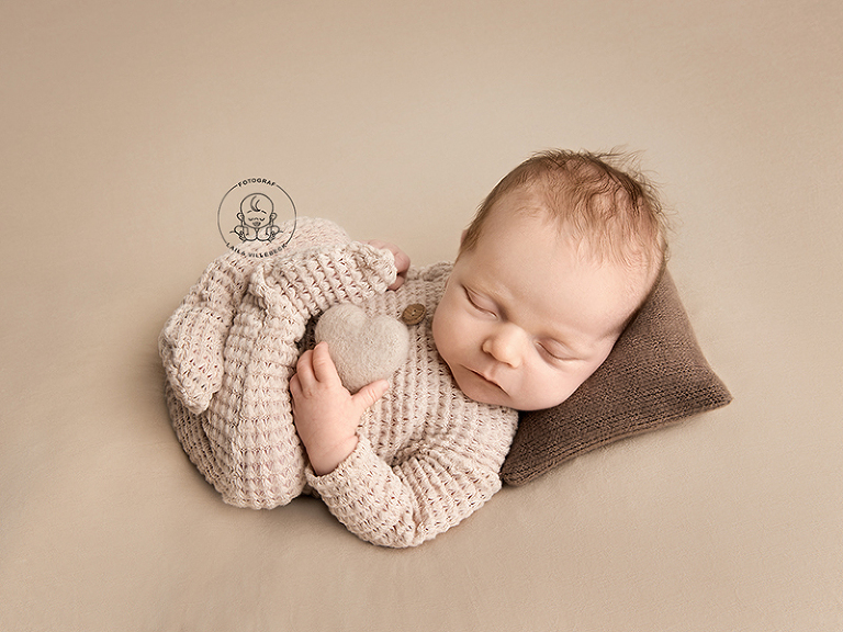 Olle, blott tre veckor, ligger på en liten kudde och sover. Benen är uppdragna och ligger på typiskt nyföddvis i kors över magen. I ena handen håller han ett hjärta. Allt i bilden går ton-i-ton i beige och brunt,