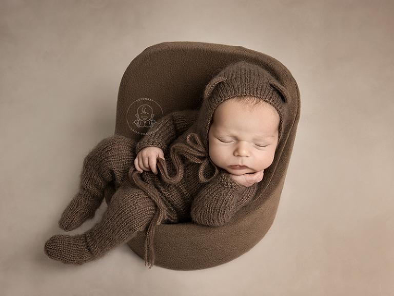 Sötaste lille Olle sitter och sover i en liten brun fåtölj i miniatyr. Han håller ena handen kring snöret från mössa han har på sig. Mössan är brun med öron och matchar den stickade outfiten med fötter.