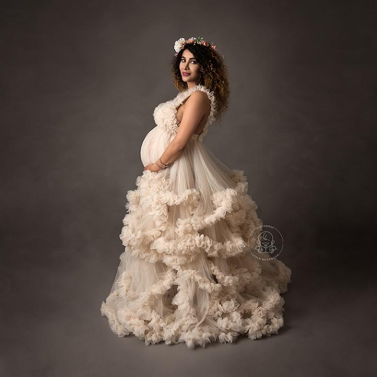 En gravid kvinna i profil. Hon bär en volymös tyllklänning i ljusbeige och har en blomkrans i håret.