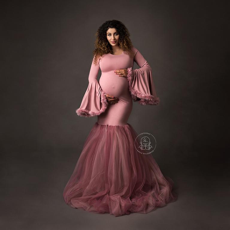 Ett helkroppsporträtt av en gravid vacker kvinna med en rosa klänning i sjöjungfrumodell med utsvängda ärmar.