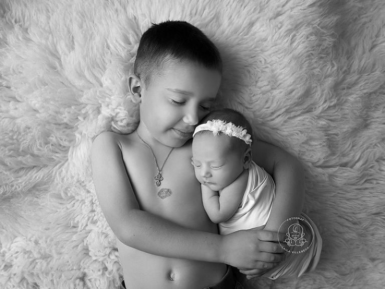 En stolt storebror kramar om sin nyfödda lillasyster. En svartvit bild där barnen ligger på en mjuk, vit fäll. Storebror har ett halsband med kors och lillasyster är inlindad.