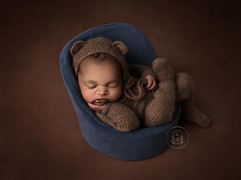 Nyfödd i stickad outfit och nallemössa sitter och sover i en fåtölj i miniatyr.