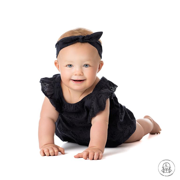 Söta Clara ligger på mage på den vita bakgrunden i fotostudion. Hon har en mörkblå klänning på sig med ett matchande hårband. Hon ler och tittar rakt in i kameran.